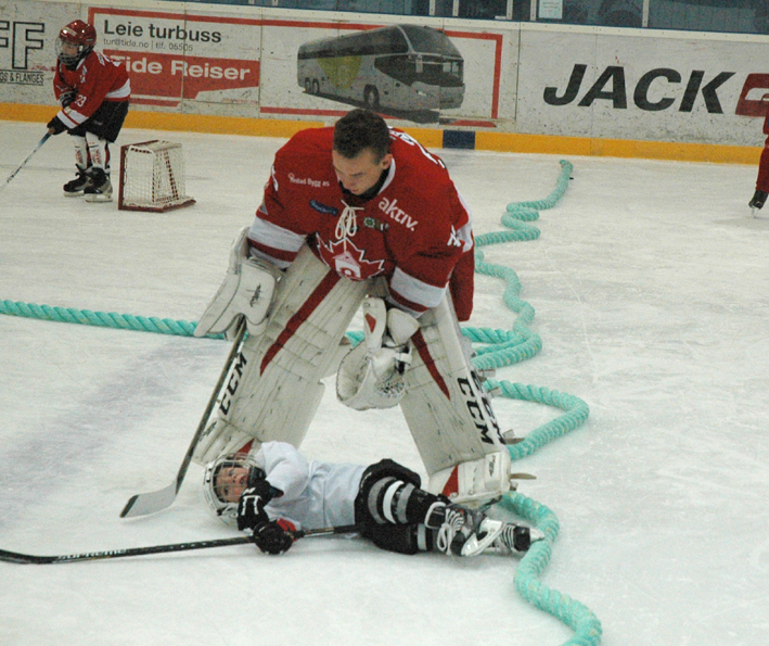BIK-keeper Fredrik Johansson hjelper opp en spiller som har falt på isen. Det gikk bra.