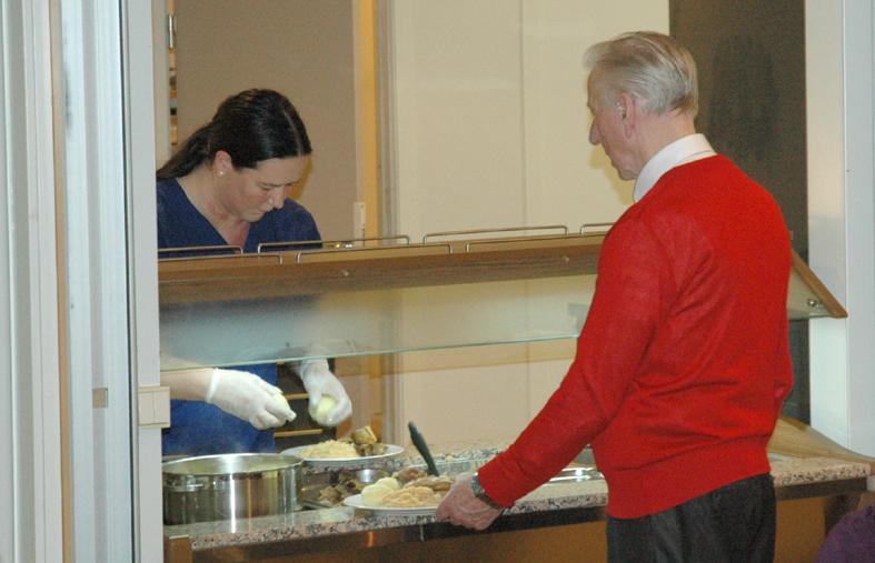 Kokk Pia Katrine Andersen legger maten på tallerkene. Frivillig pensjonisthjelp Karl Erichsen står klar til å få maten raskest mulig på bordet.