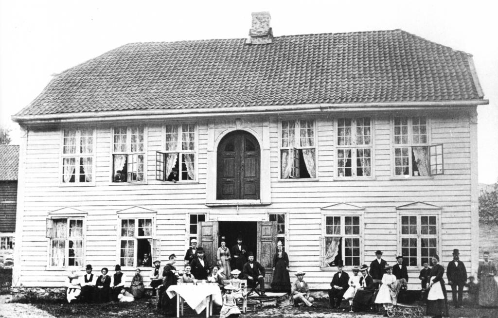"""Våningshuset på gården Mandsverk på begynnelsen av 1880-tallet med familiene Fasmer og Hagelsteen foran. Beboerne på gården ble trolig ikke gravlagt på kirkegården i Wiers-Jenssens vei. Legg merke til forskjell i klesdrakt mellom de """"fine"""" byfolkene og de fem """"bondefolkene"""" til venstre i bildet. Gårdsbygningene ble revet i 1956 ved utbyggingen av Mannsverk. Bildet er hentet fra boken «Landås. Fra lystgårder og husmannsplasser til drabantby», Kanonhaugen Forlag."""