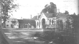 Haukeland hovedgård med portalen og vakten til sykehuset i forgrunnen. Bildet er tatt i 1912. Fotograf ukjent. Arkivet etter Byggekomiteen for Haukeland sykehus, Bergen Byarkiv.