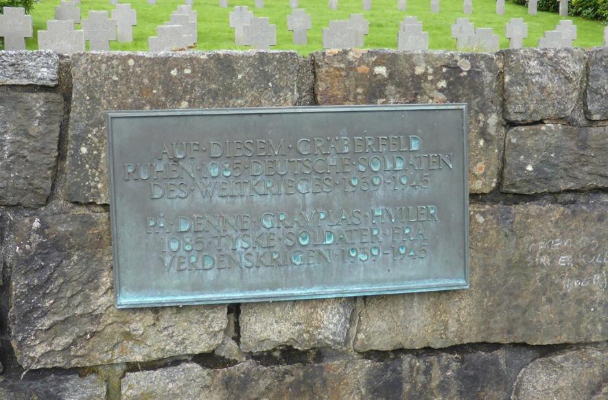 """Ved inngangen til det tyske gravfeltet på Solheim er det satt opp en bronseplakett med påskriften """"Auf diesem gräberfeld ruhen 1085 deutsche soldaten des weltkriges 1939-1945"""". """"På denne gravplassen hviler 1085 tyske soldater fra verdenskrigen 1939-1945""""."""